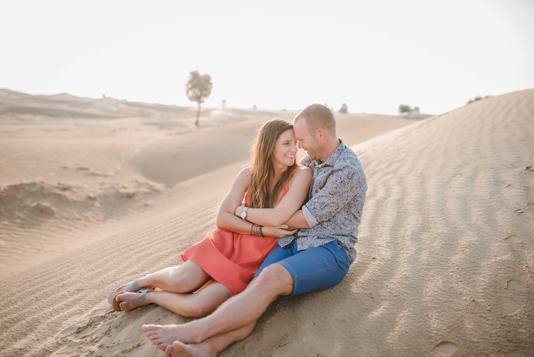 Couple sitting together on a sand dune and hugging at Al Qudra Lake on a couples trip to Dubai