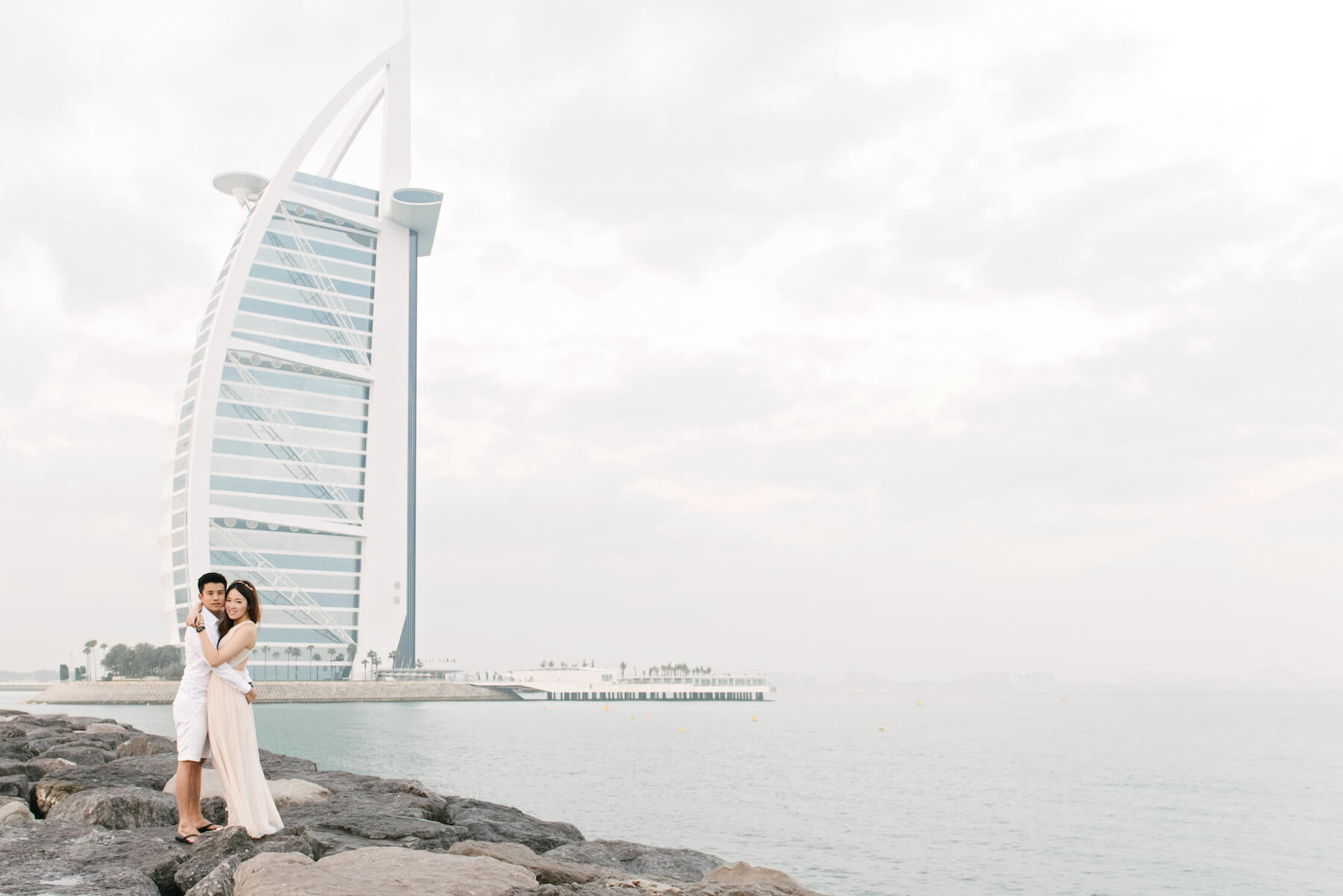 Couple hugging and standing on rocks near water with the Burj Al Arab Jumeirah skyscraper in the background in Dubai