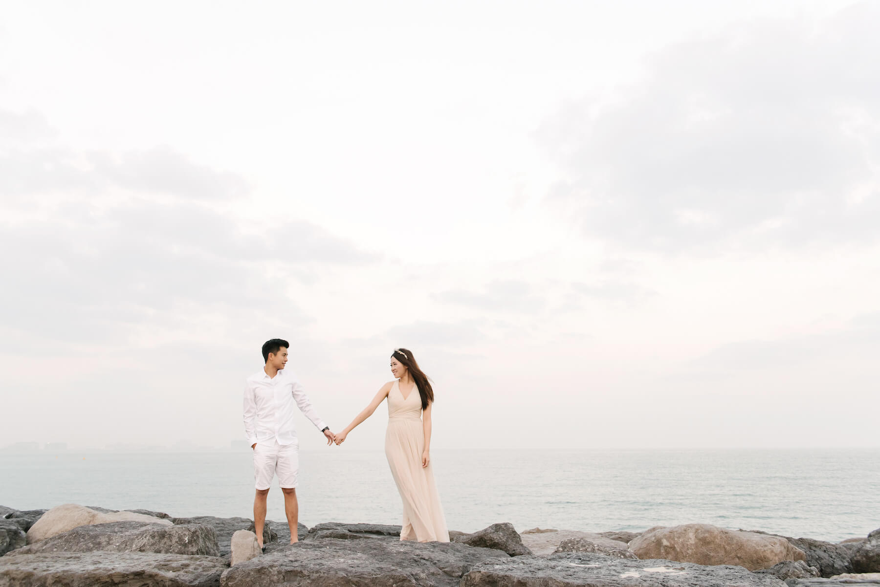 Couple holding hands and standing on rocks by the water on a couples trip in Dubai
