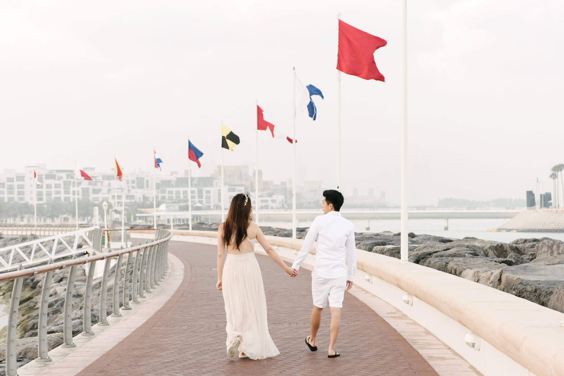 Couple holding hands and walking along boardwalk on a couples trip in Dubai