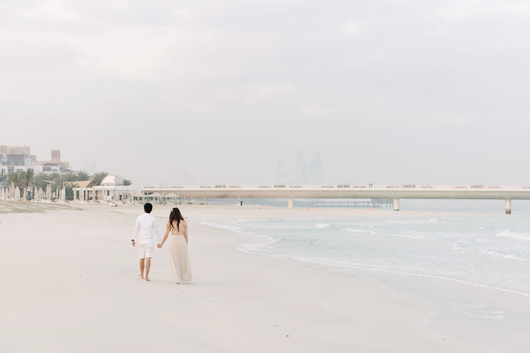 Couple holding hands and walking along the Jumeirah Beach sand in Dubai