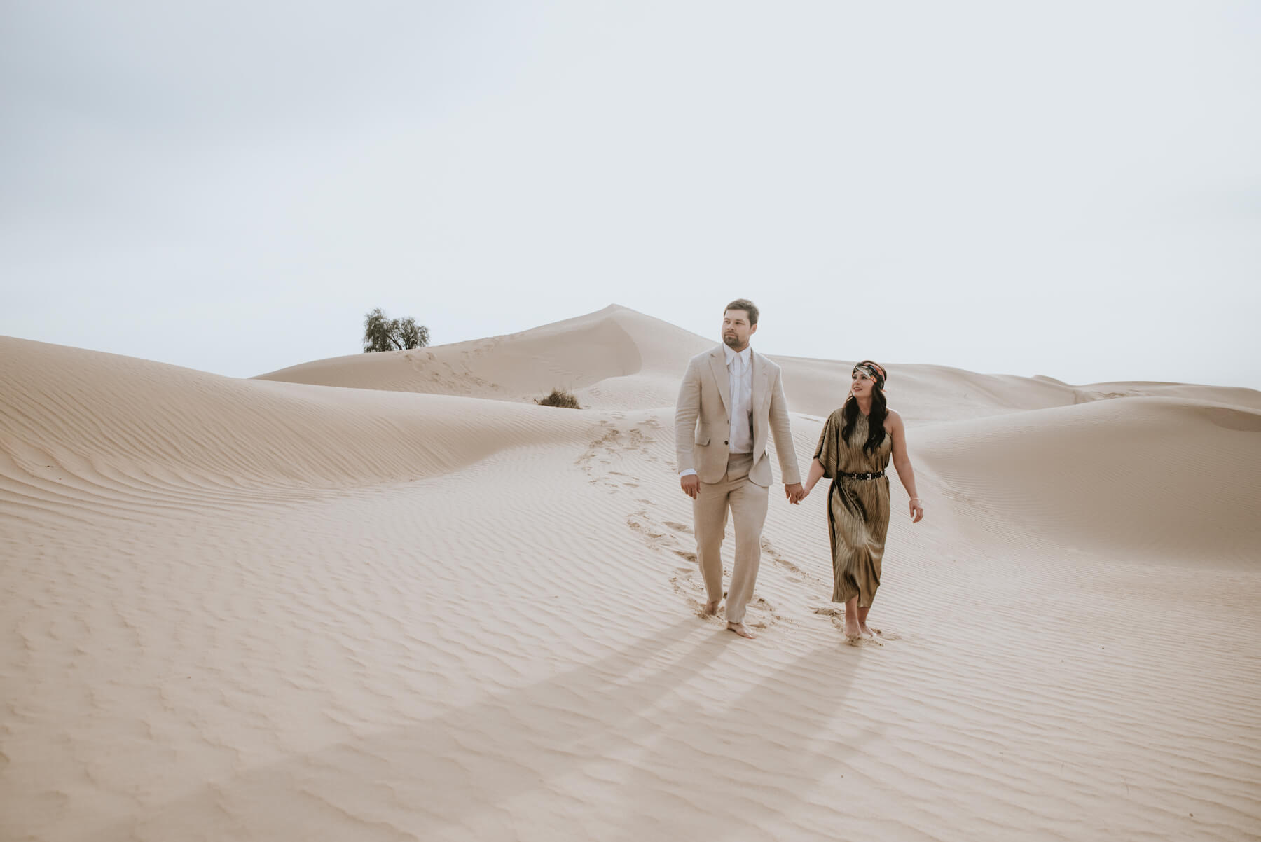 A couple walking the Dubai Desert Conservation Reserve on a couples photoshoot with Flytographer.