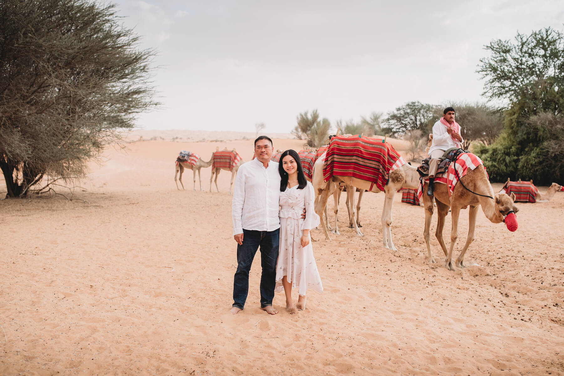 A couple with camels and tour guide in the Dubai desert in Dubai, United Arab Emirates