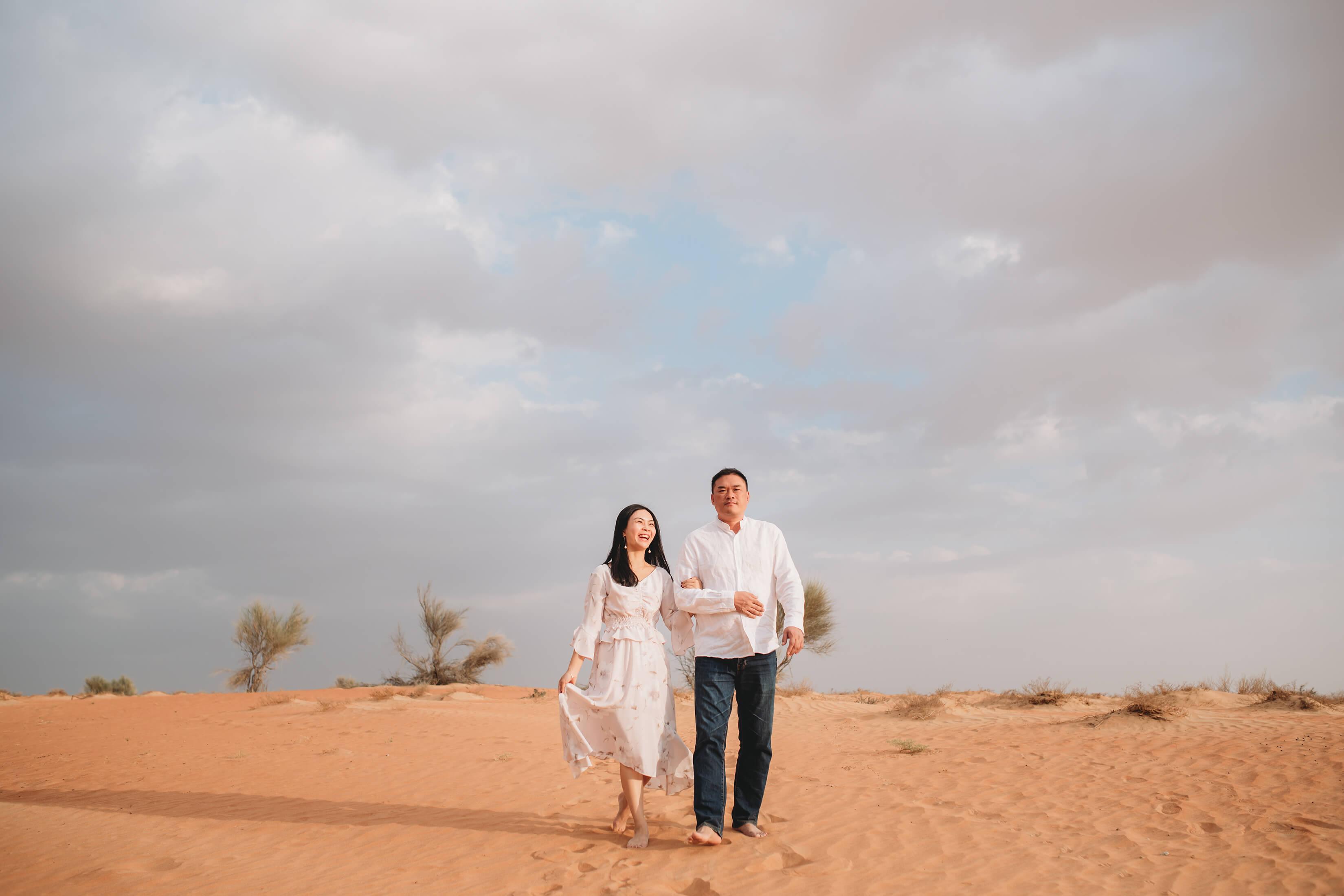 A couple walking in the Dubai desert in Dubai, United Arab Emirates