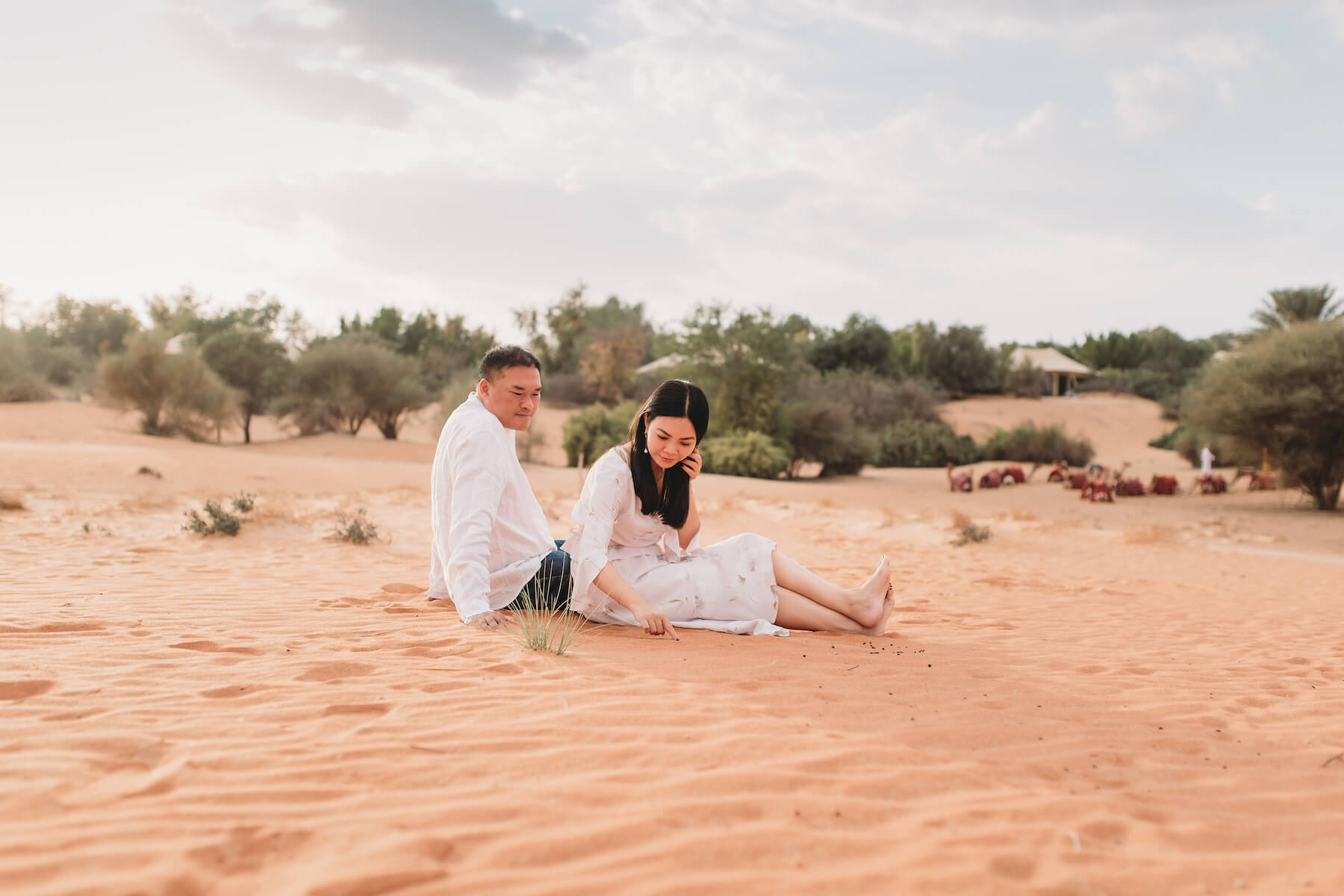 Two people each sitting in the Dubai desert in Dubai, United Arab Emirates