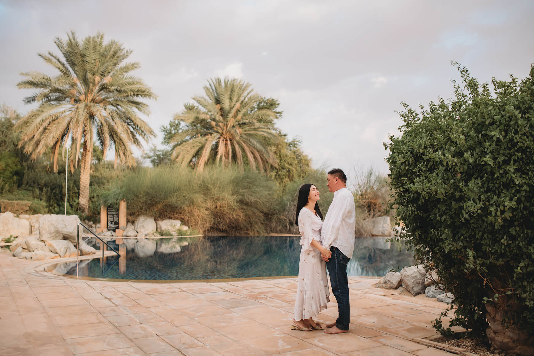 Asian couple hugging each other and laughing on a couples trip to Dubai, United Arab Emirates
