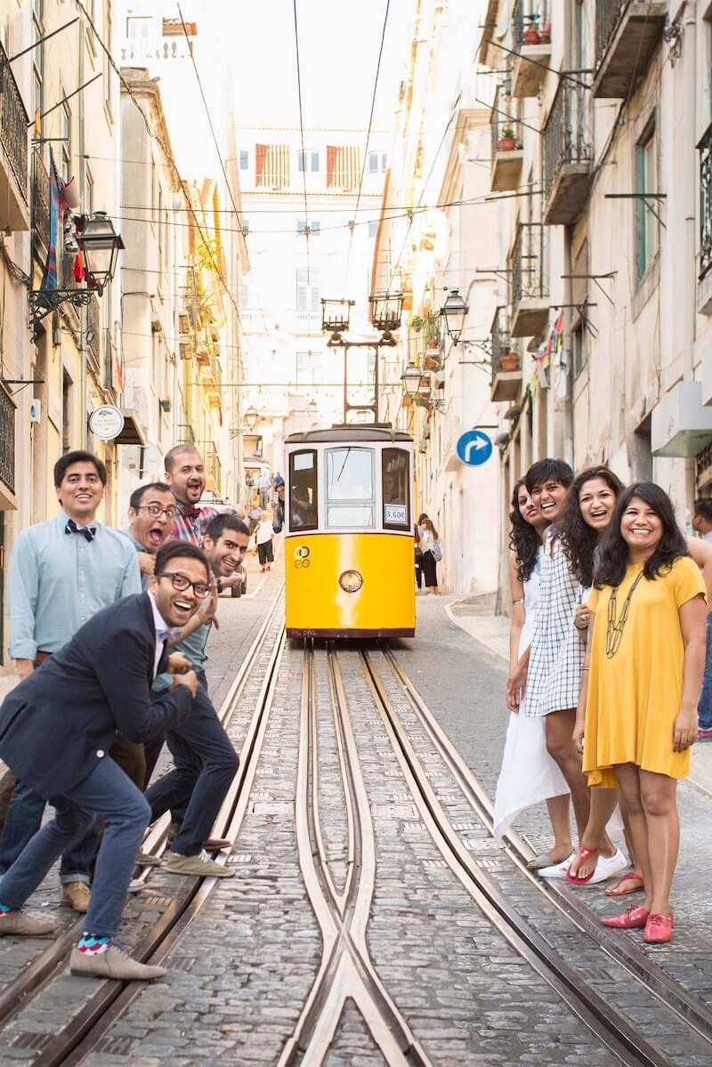 Family of nine smiling and pointing at a yellow trolley in the Bica district of Lisbon, Portugal