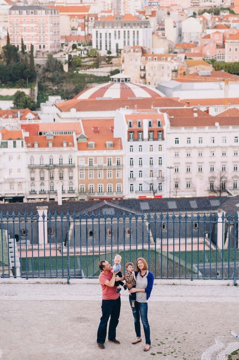 Family of four with two young sons smiling at the Miradouro de São Pedro de Alcântara in Lisbon, Portugal