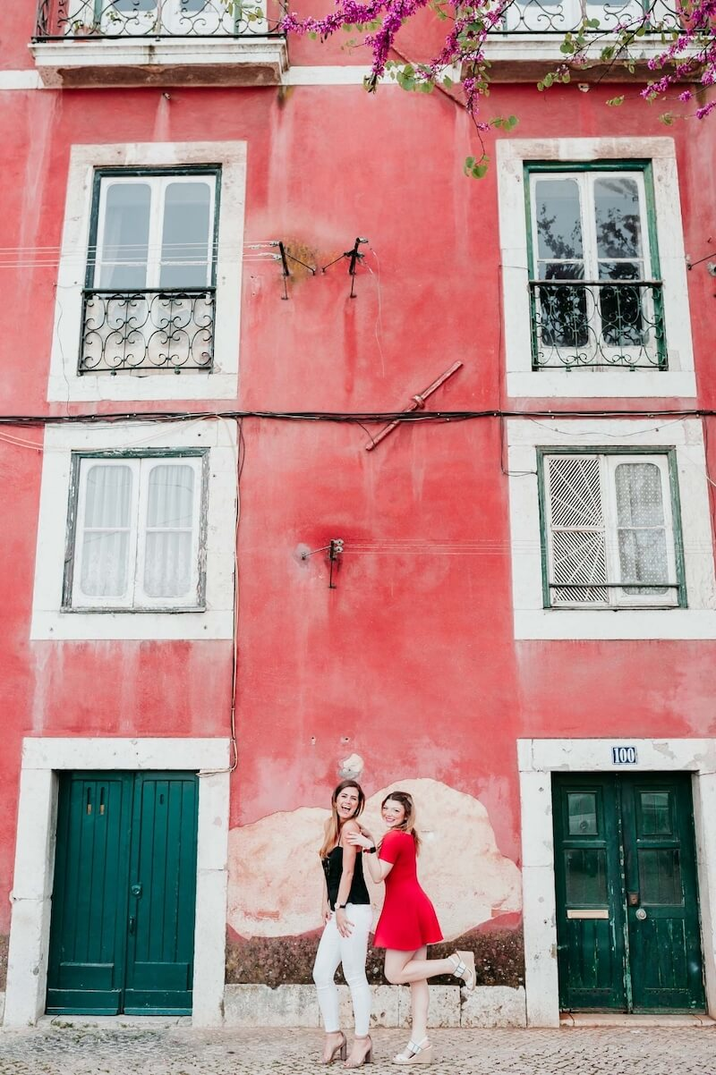 Two female friends standing together in front of a bright red building on a friends trip in Lisbon, Portugal