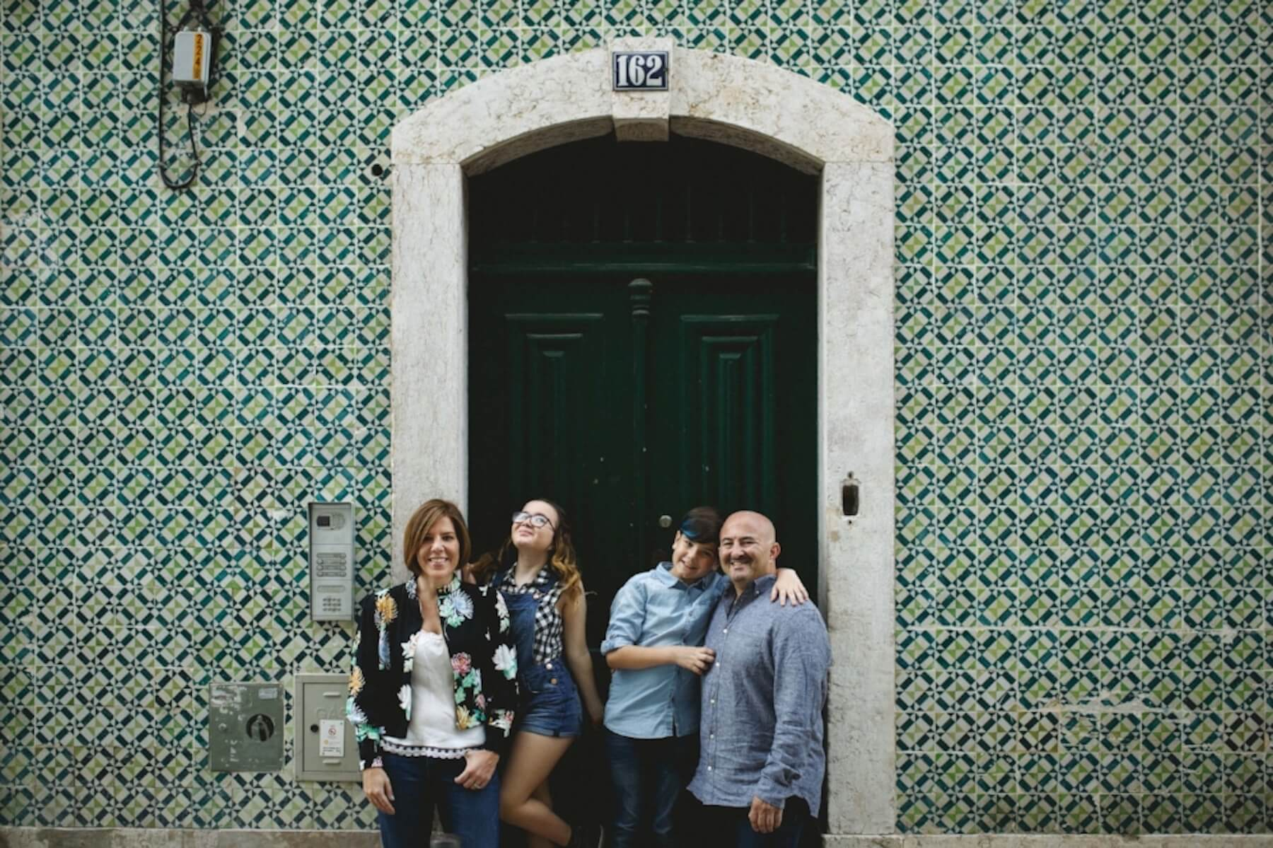 Family of four with two pre-teen children standing in front of building with green and blue Portuguese tile in Lisbon, Portugal