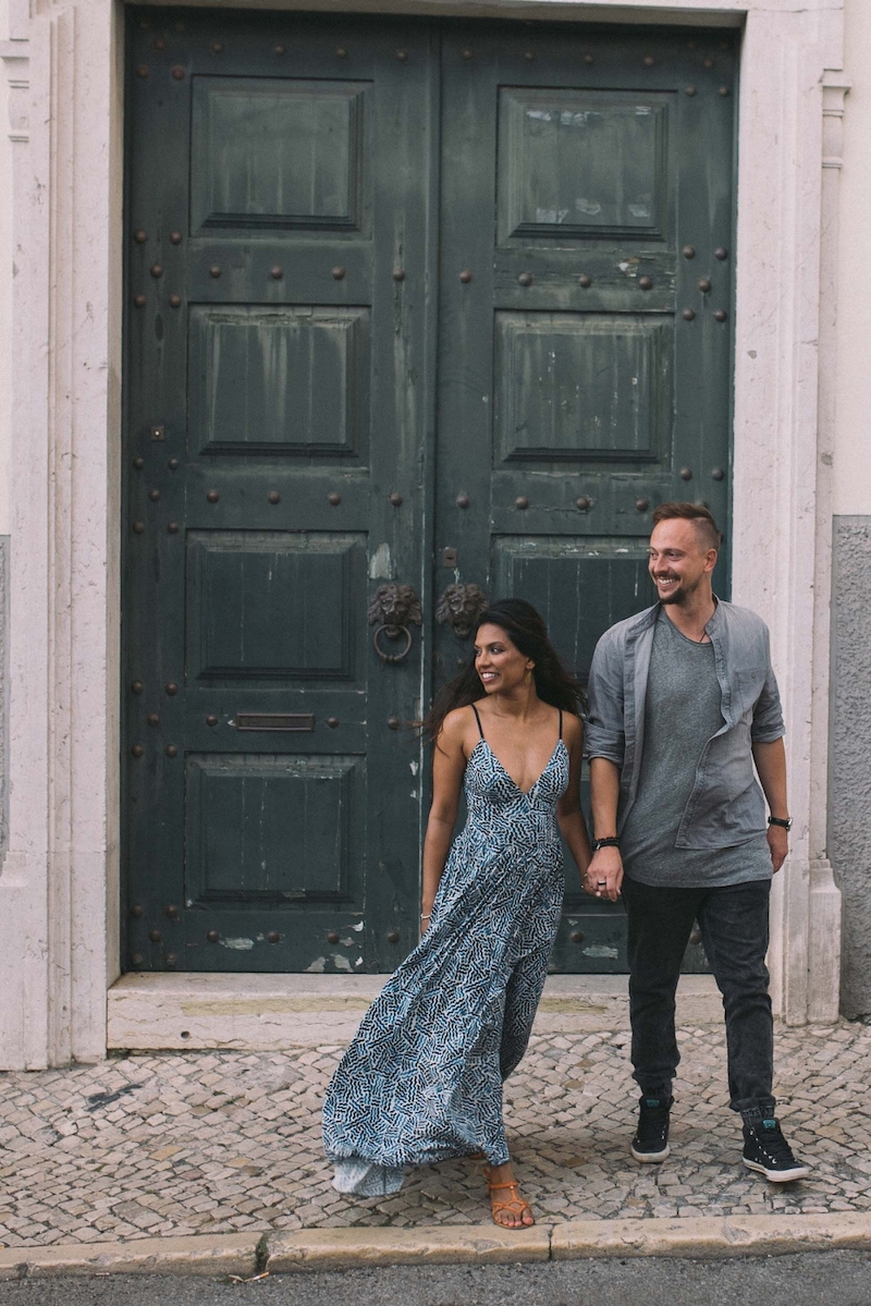 Couple standing in front of large green doorway and holding hands, smiling together in Lisbon, Portugal