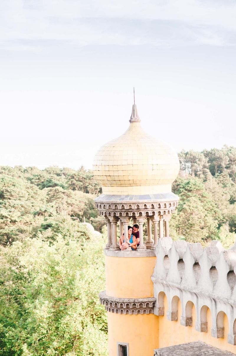 Couple standing in yellow pastel tower in the National Palace of Pena in Sintra, Portugal
