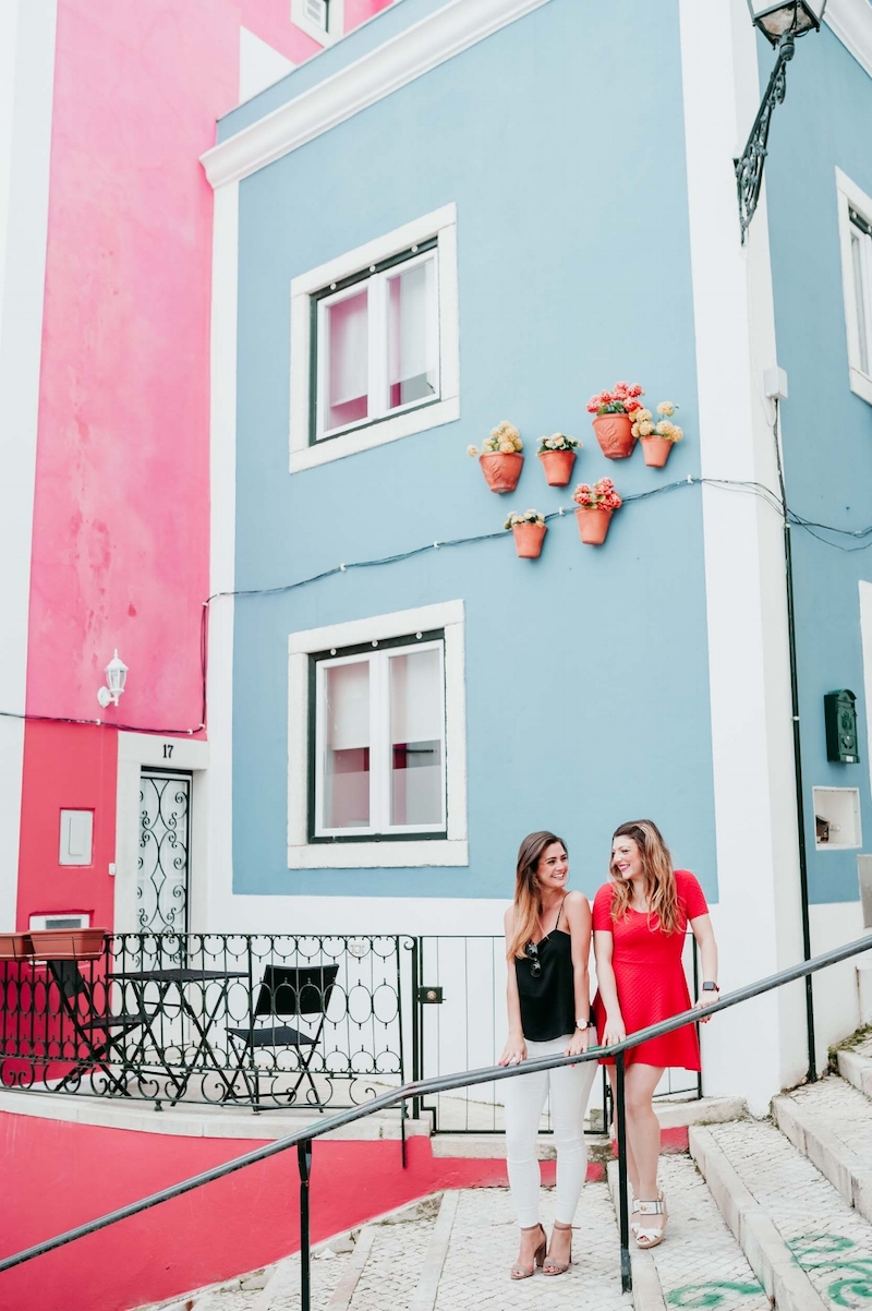 Friends smiling at each other while standing on some steps in the Rua da Galé district of Lisbon, Portugal