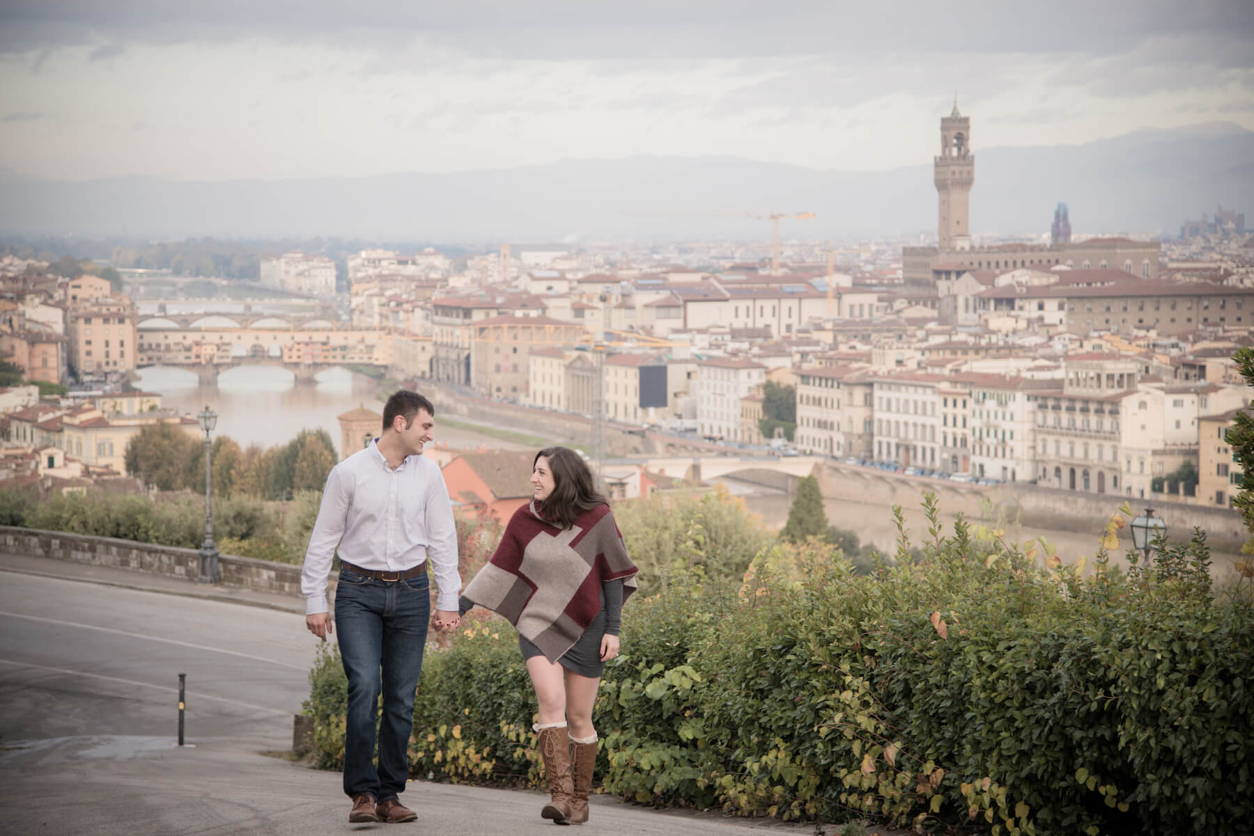 Couple holding hands walking uphill in Florence, Italy