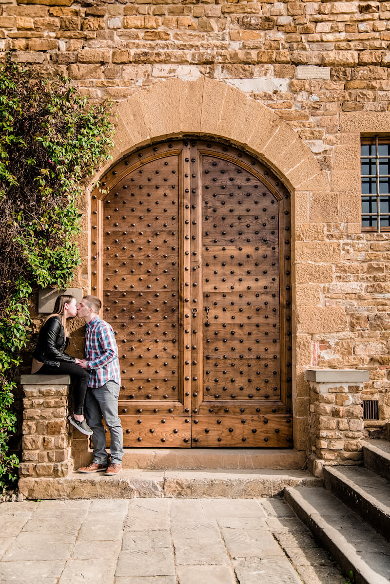 Couple kissing in front of iron studded door in Florence, Italy