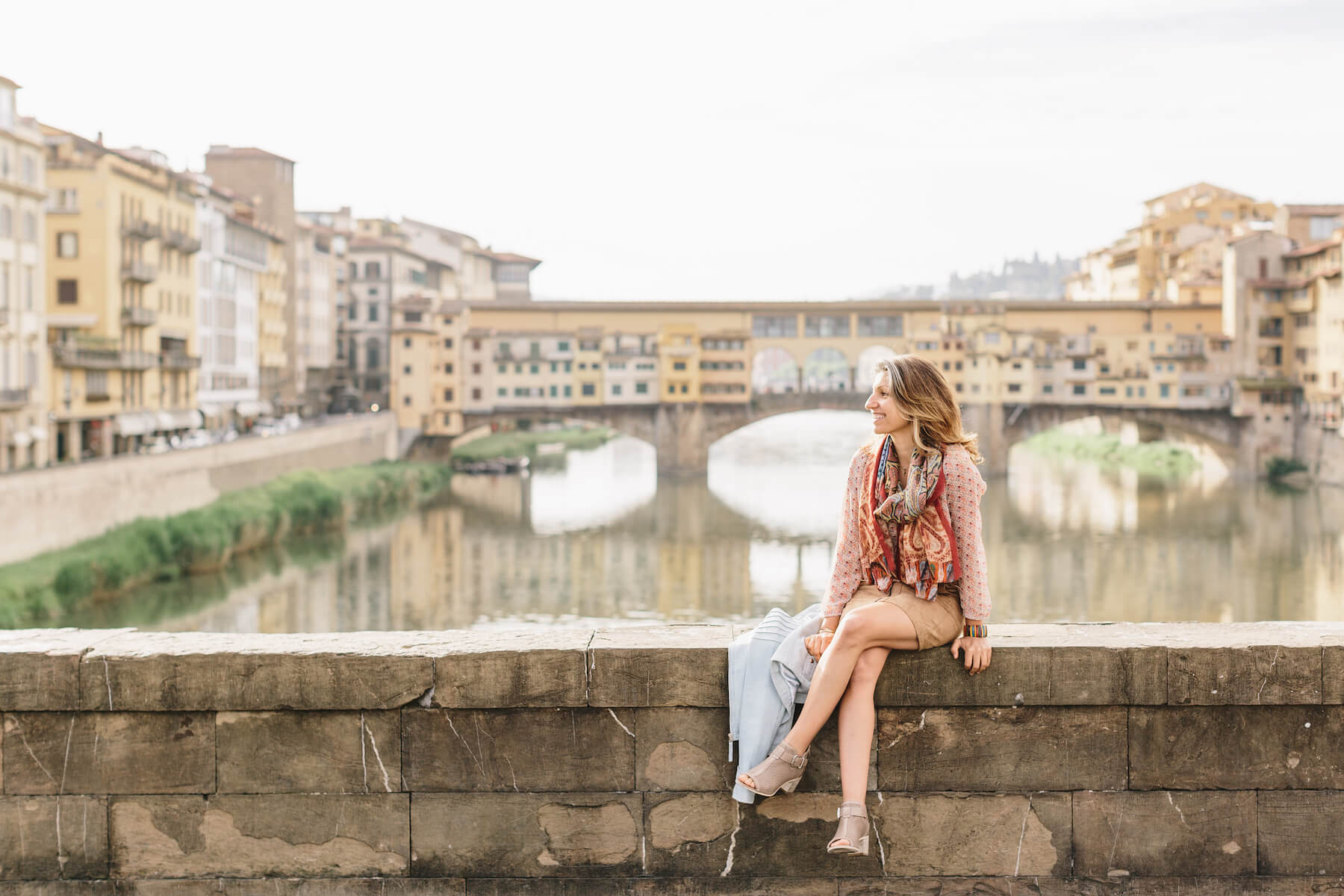 Solo female traveller smiling near Ponte Vecchio on solo trip in Florence, Italy