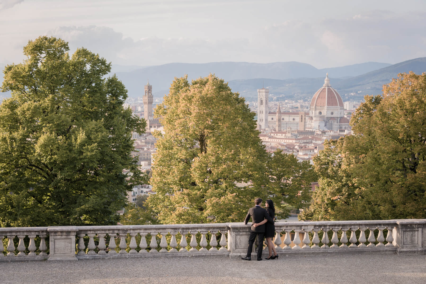 Couple hugging and looking over the city of Florence, Italy