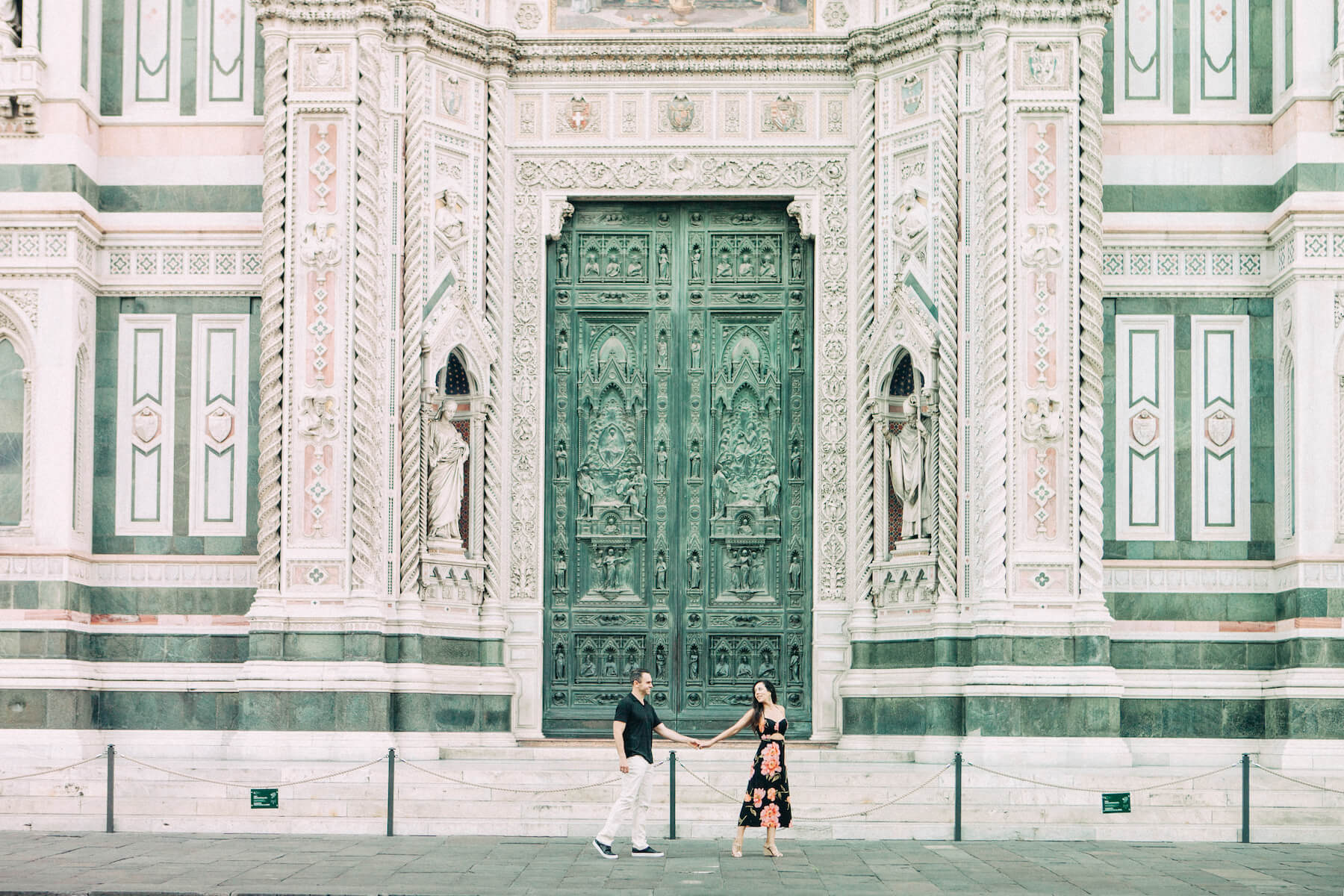 Couple holding hands and walking in front of The Duomo in Florence, Italy