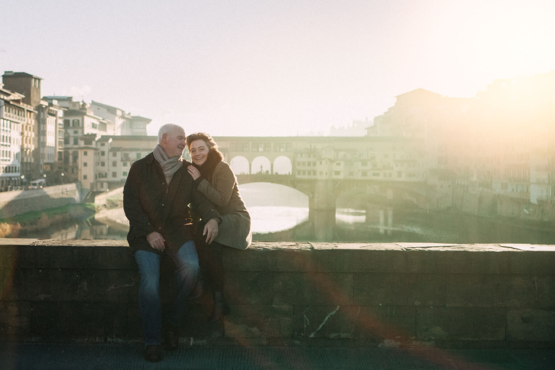 Mature couple sitting together in the winter on bridge ledge in front of Ponte Vecchio in Florence, Italy