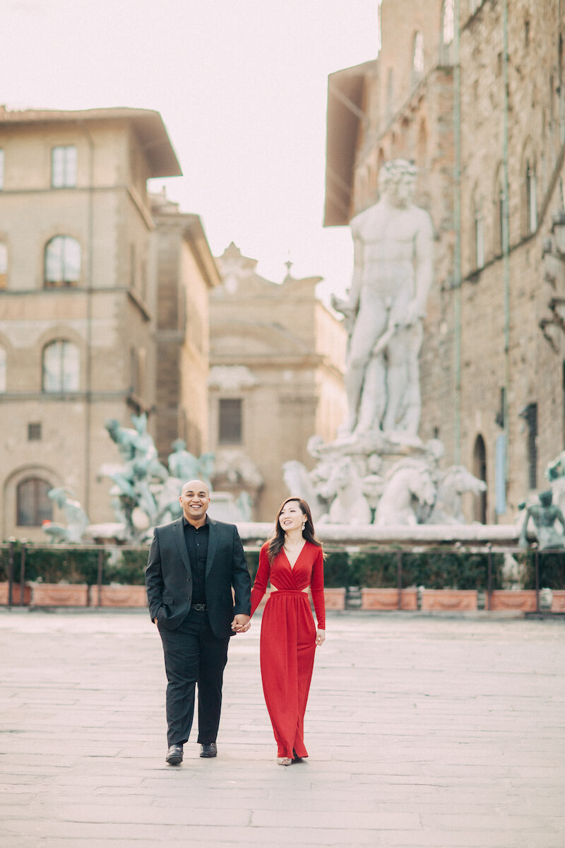 Couple holding hands and walking in front of the fountain of Neptune at Piazza della Signoria in Florence, Italy