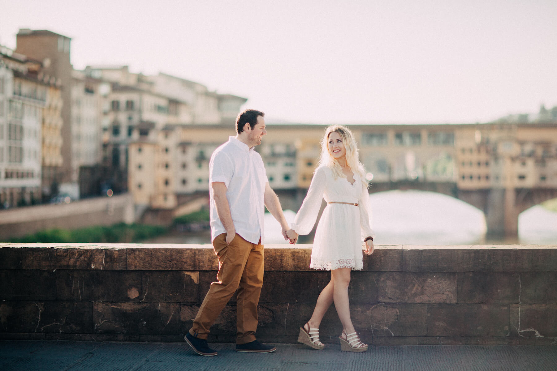 Couple holding hands and walking on bridge in front of Ponte Vecchio in Florence, Italy