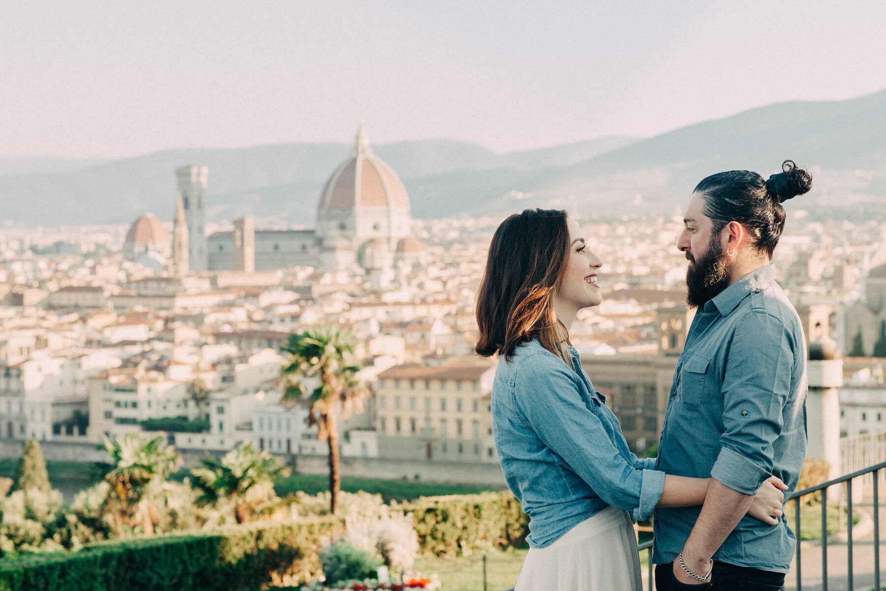 Couple hugging and overlooking the city at Piazzale Michelangelo in Florence, Italy