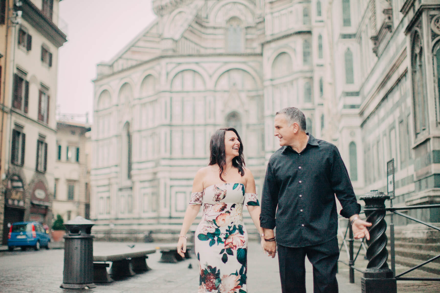 Mature couple holding hands and smiling at each other in front of The Duomo on a couples trip in Florence, Italy