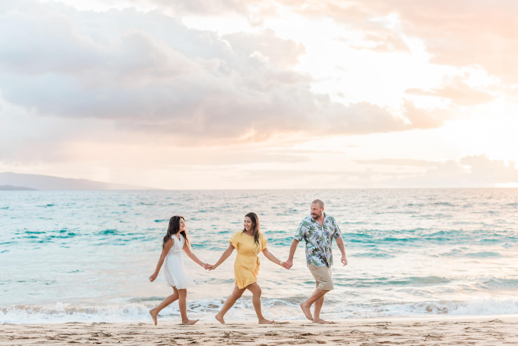 Family of three holding hands and walking in the water together in Maui, USA