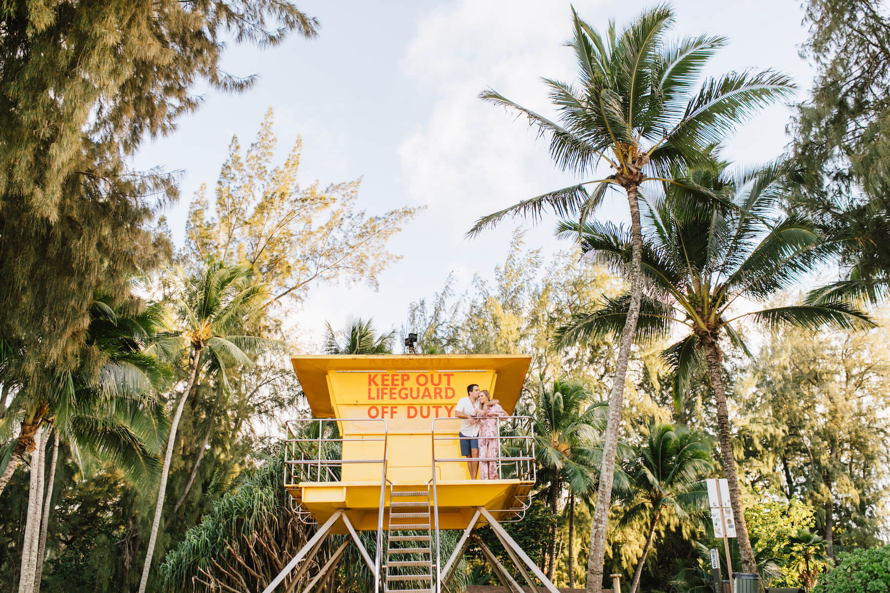 couple standing on a lifeguard tower on the beach in Maui, Hawaii