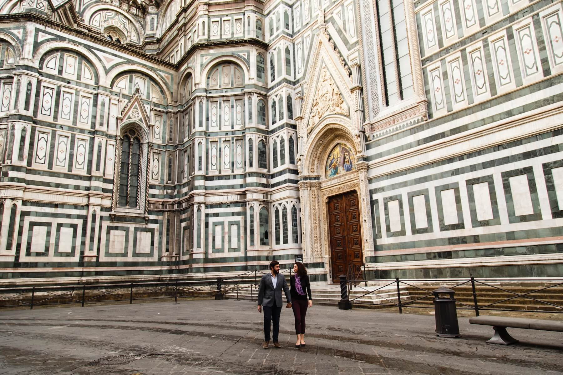 Couple holding hands walking together in front of The Duomo on couples trip in Florence, Italy