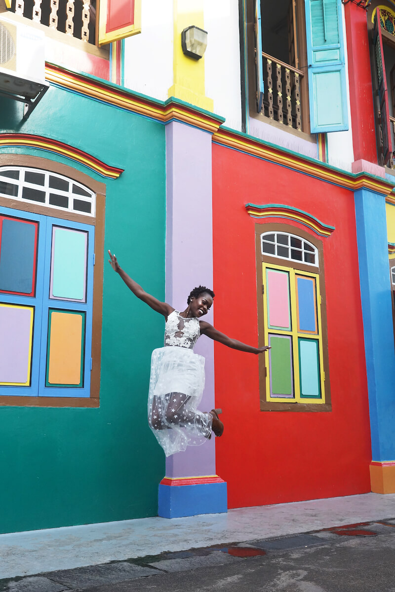 Woman jumping in the air in front of bright coloured building in Singapore