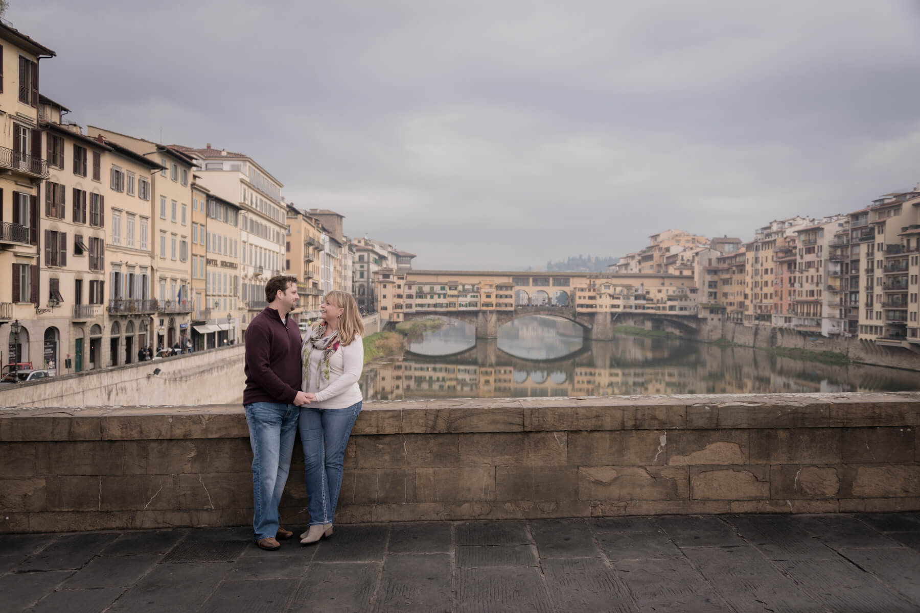 Couple looking lovingly at each other on a trip together at Ponte Vecchio in Florence, Italy