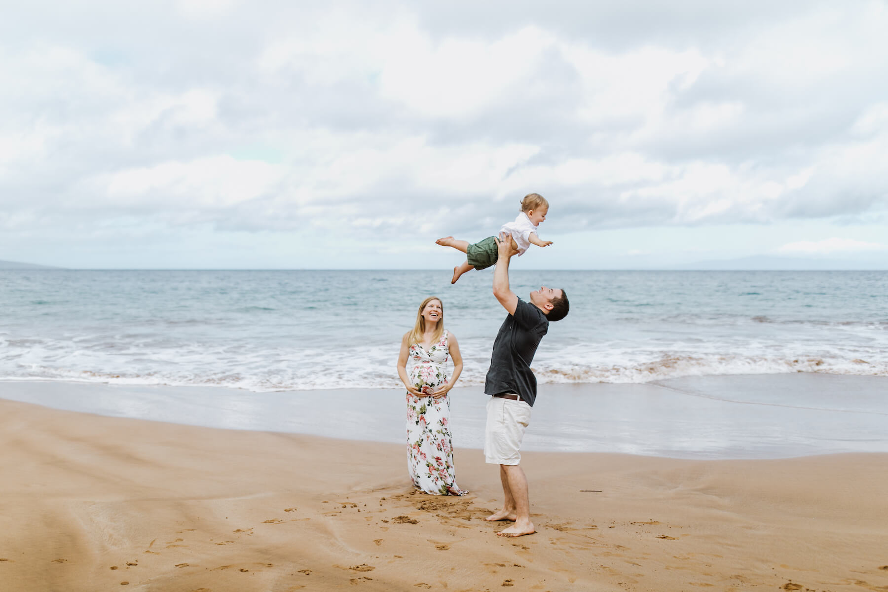 family on the shoreline waves together in Maui, USA