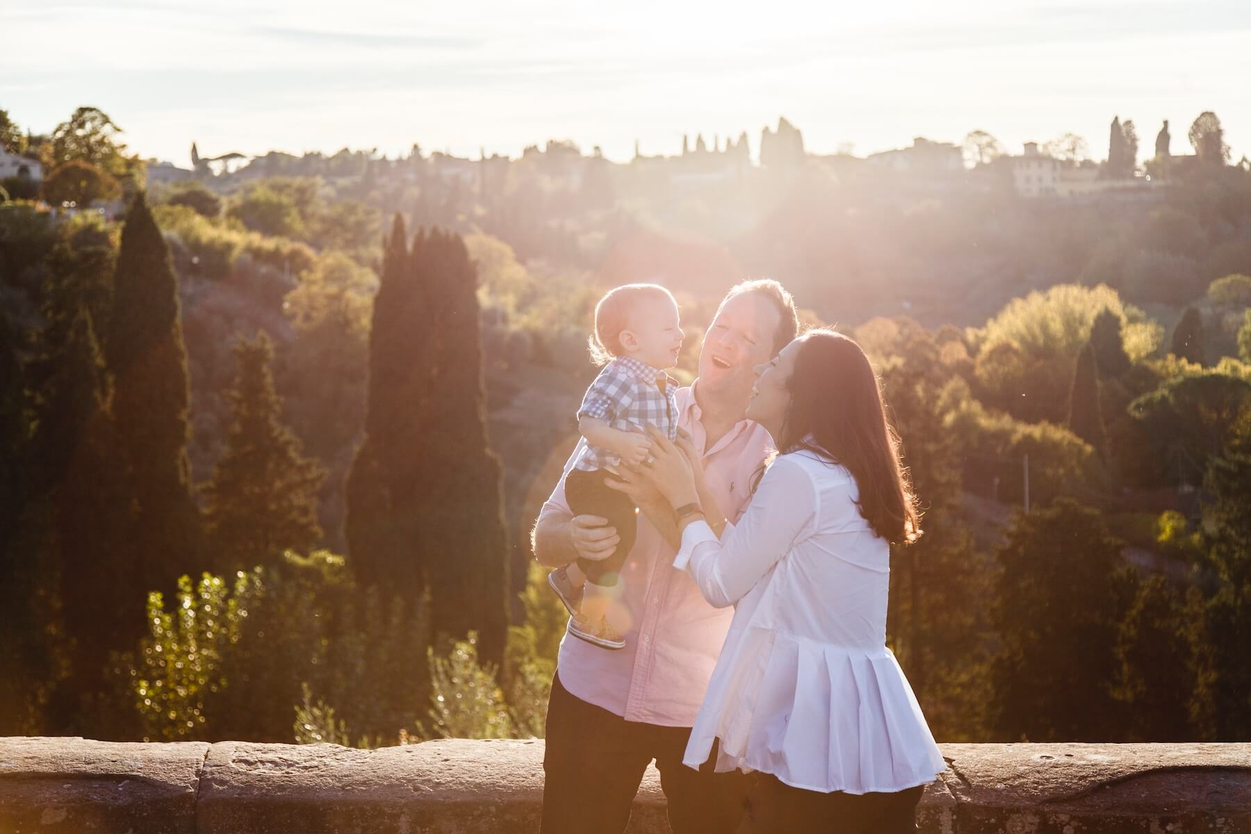 Father and mother holding infant son, all smiling together on a family trip in Florence, Italy