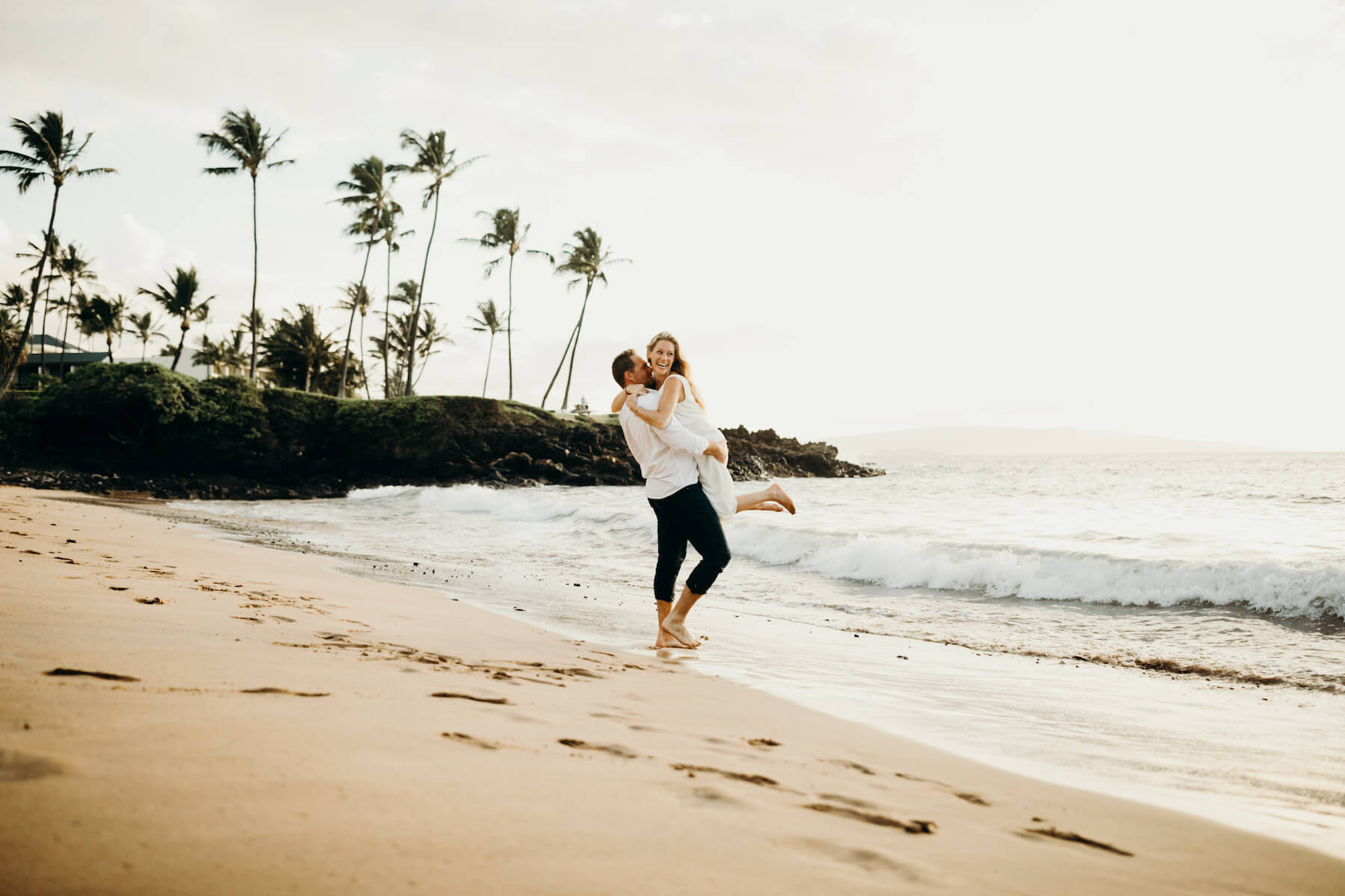 Couple having fun, the woman is being lifted along a sandy shoreline in Maui, USA