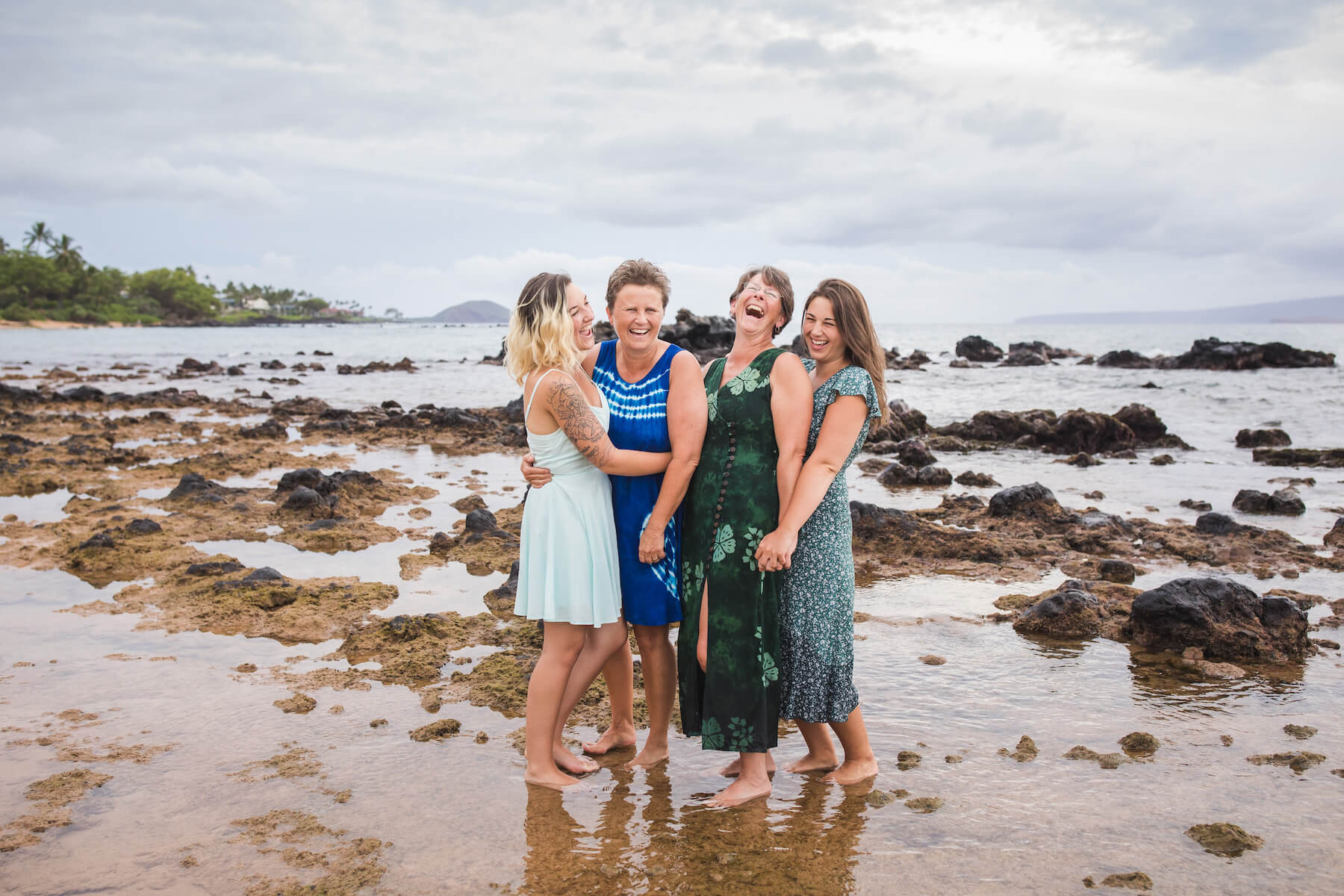 LGBTQ Family of 4 holding each other and laughing on the beach in Maui, USA