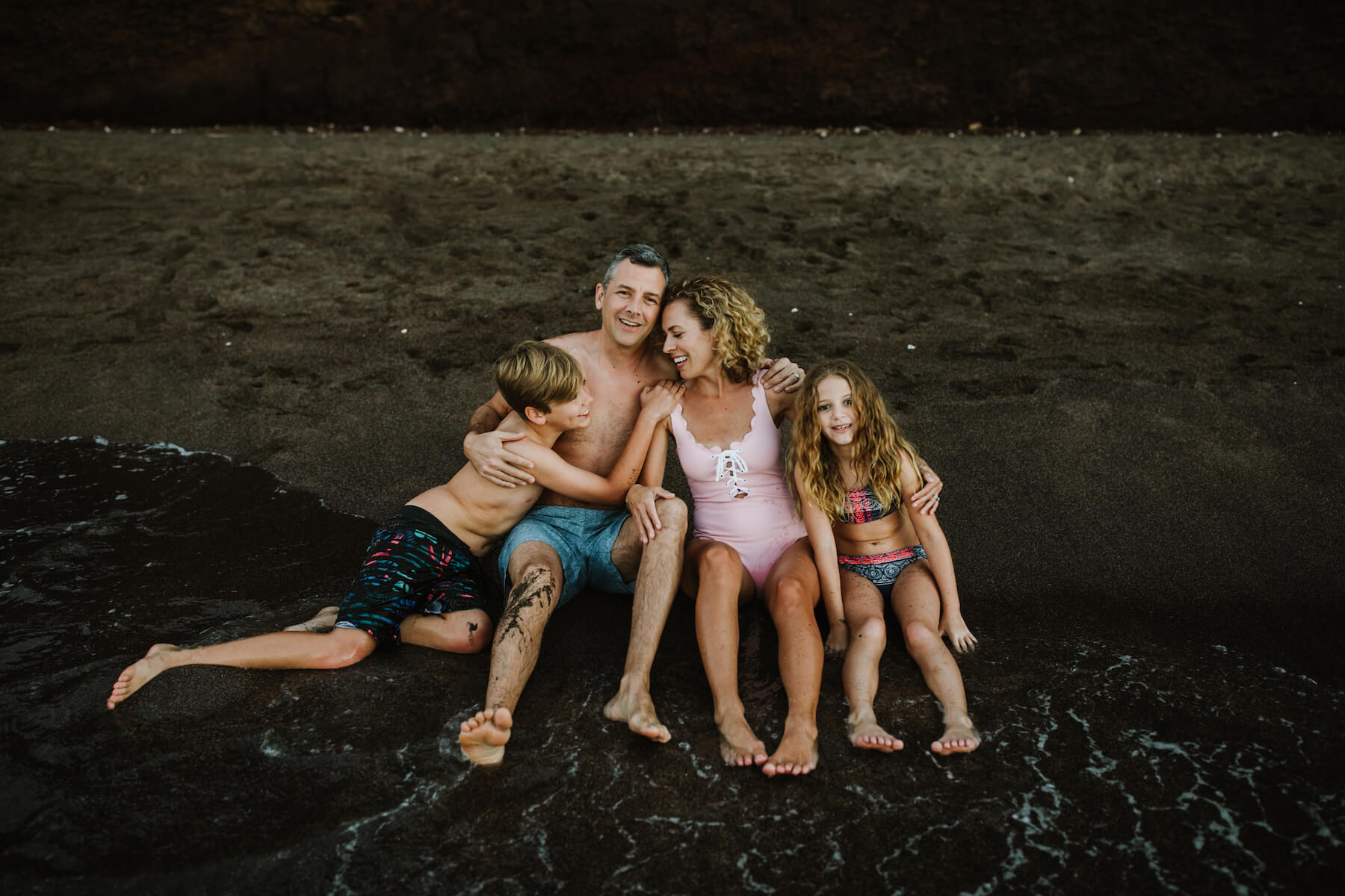 Family of four sitting on a black sand beach in Maui, Hawaii USA