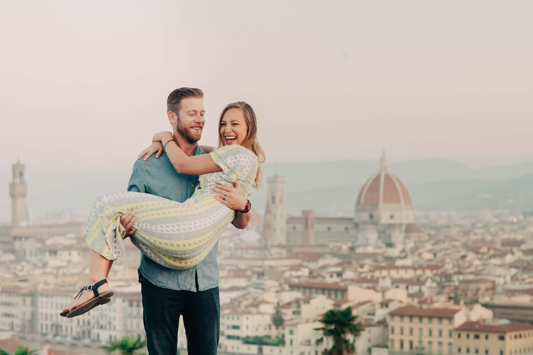 Man holding partner in his arms at Piazzale Michelangelo in Florence, Italy