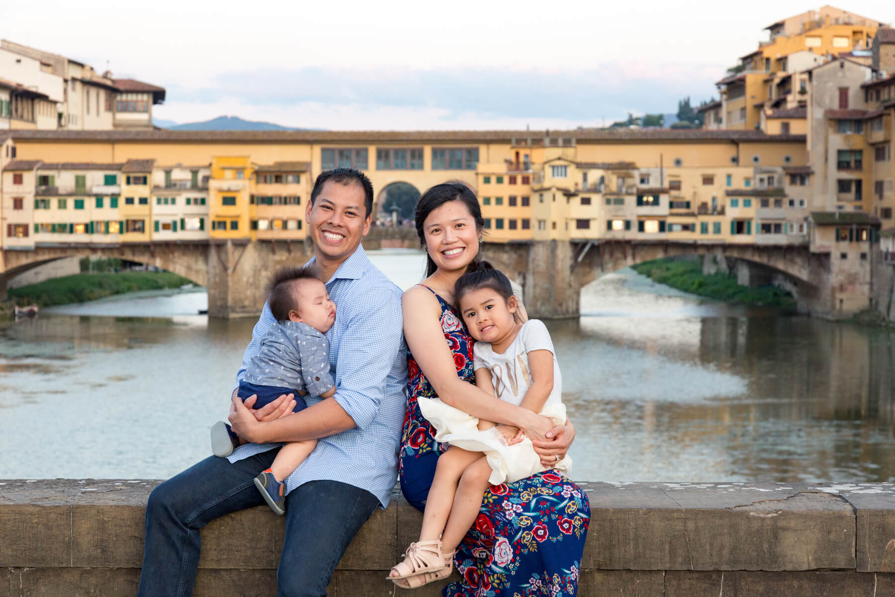 Happy asian family with two children sitting on bridge ledge at Ponte Vecchio in Florence, Italy