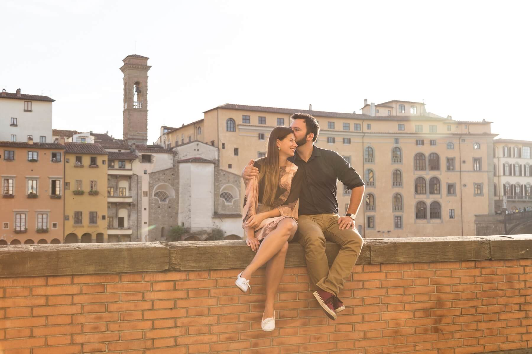 Couple sitting on wall ledge together kissing on couples trip in Florence, Italy