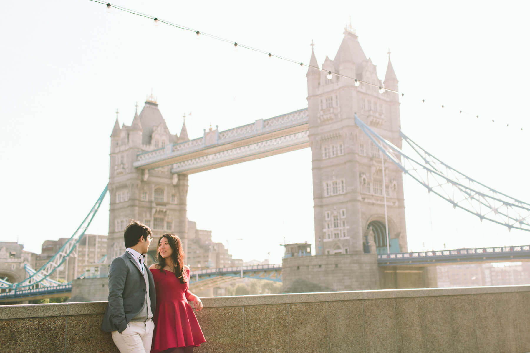 Couple looking lovingly at each other with the Tower Bridge in the background in London, UK
