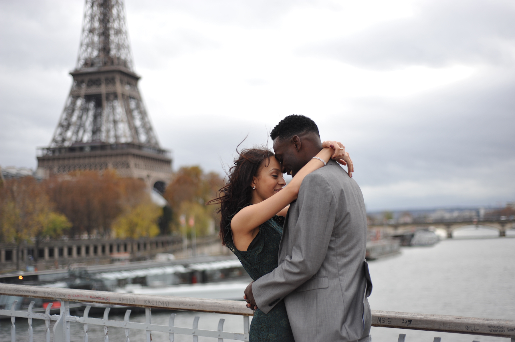 Couple hugging each other with the Eiffel Tower in the background in Paris, France