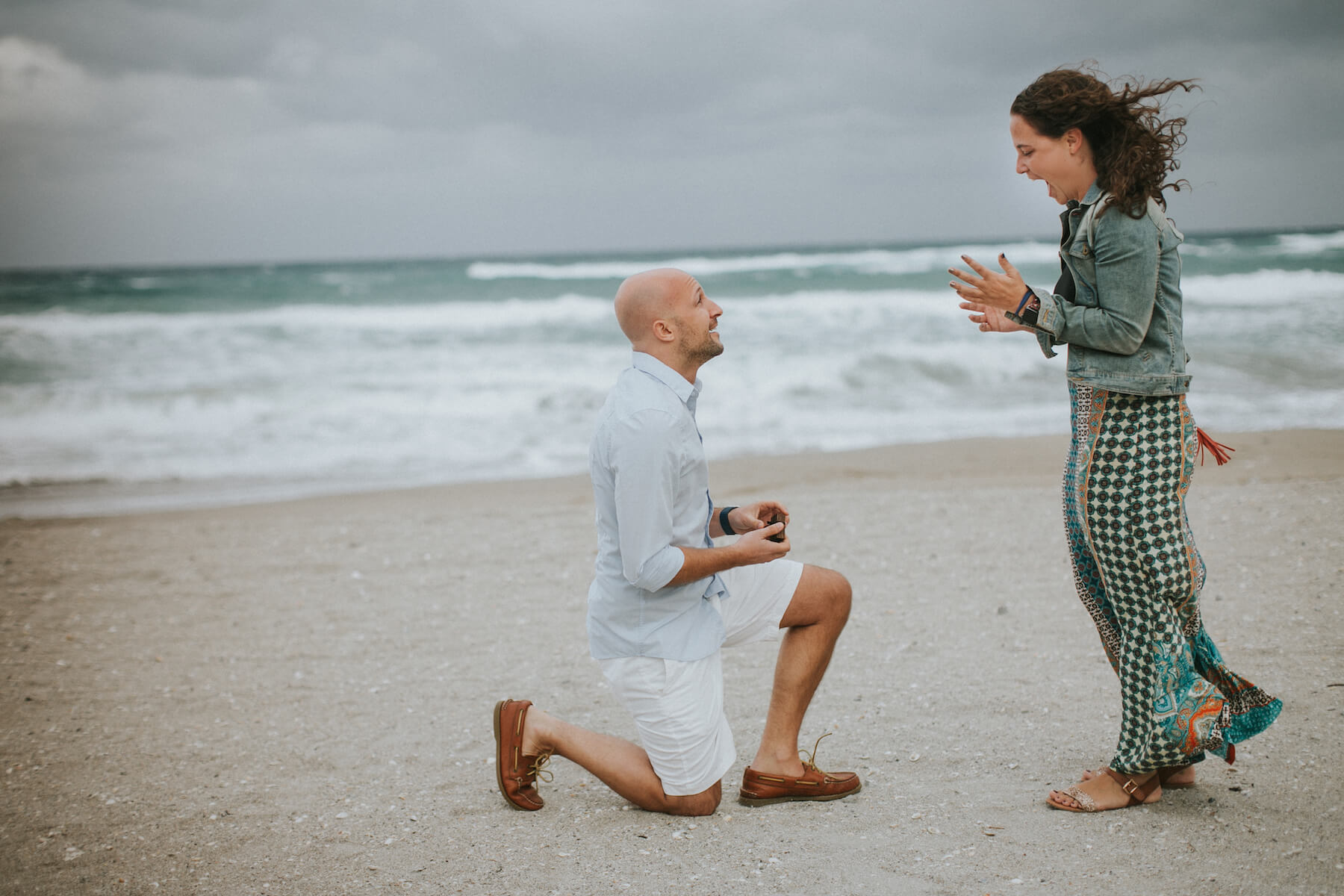 Woman surprised at surprise Flytographer proposal while her partner presents her engagement ring in Miami, Florida USA