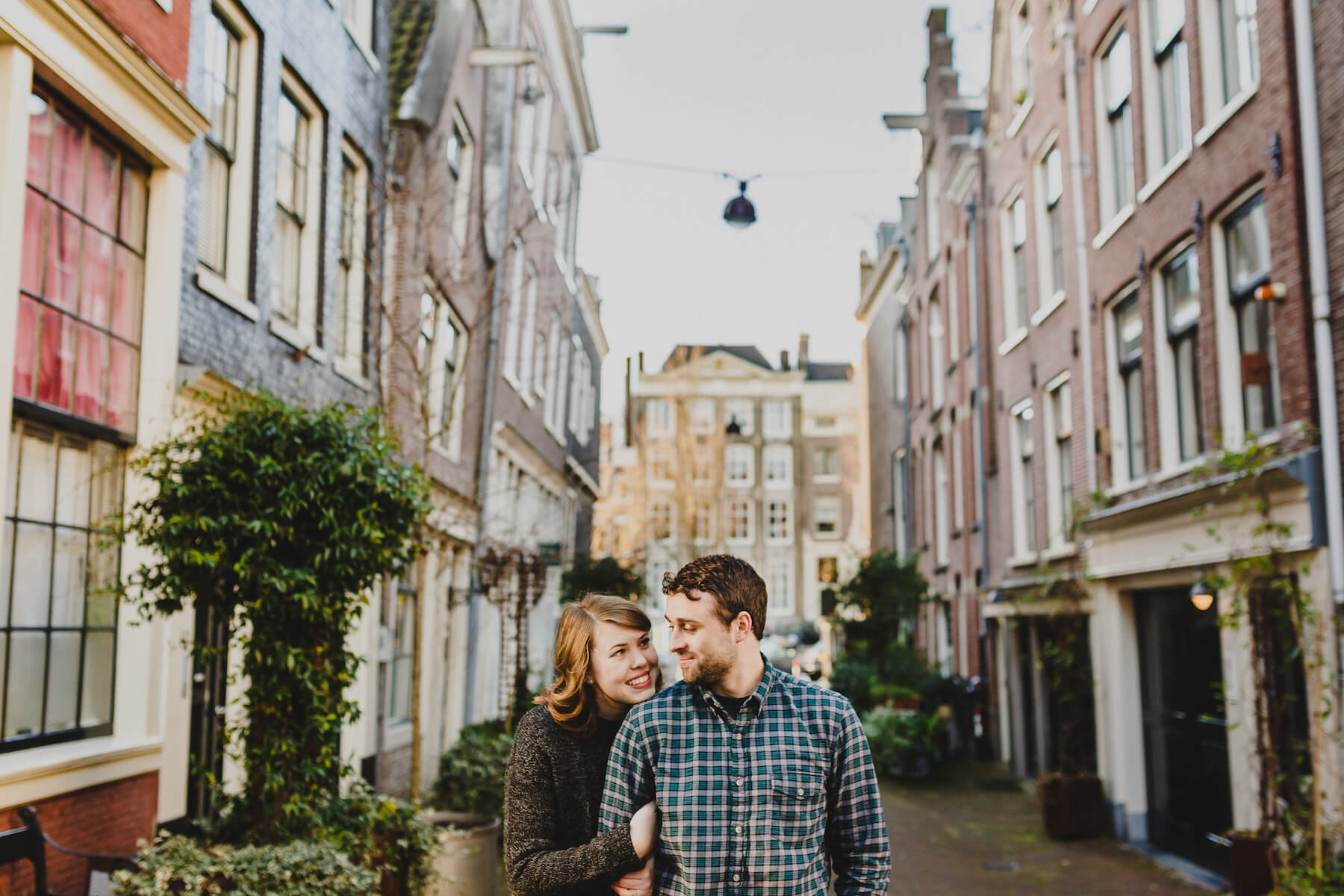 Couple looking at each other lovingly while standing in a small alleyway in Amsterdam, Netherlands