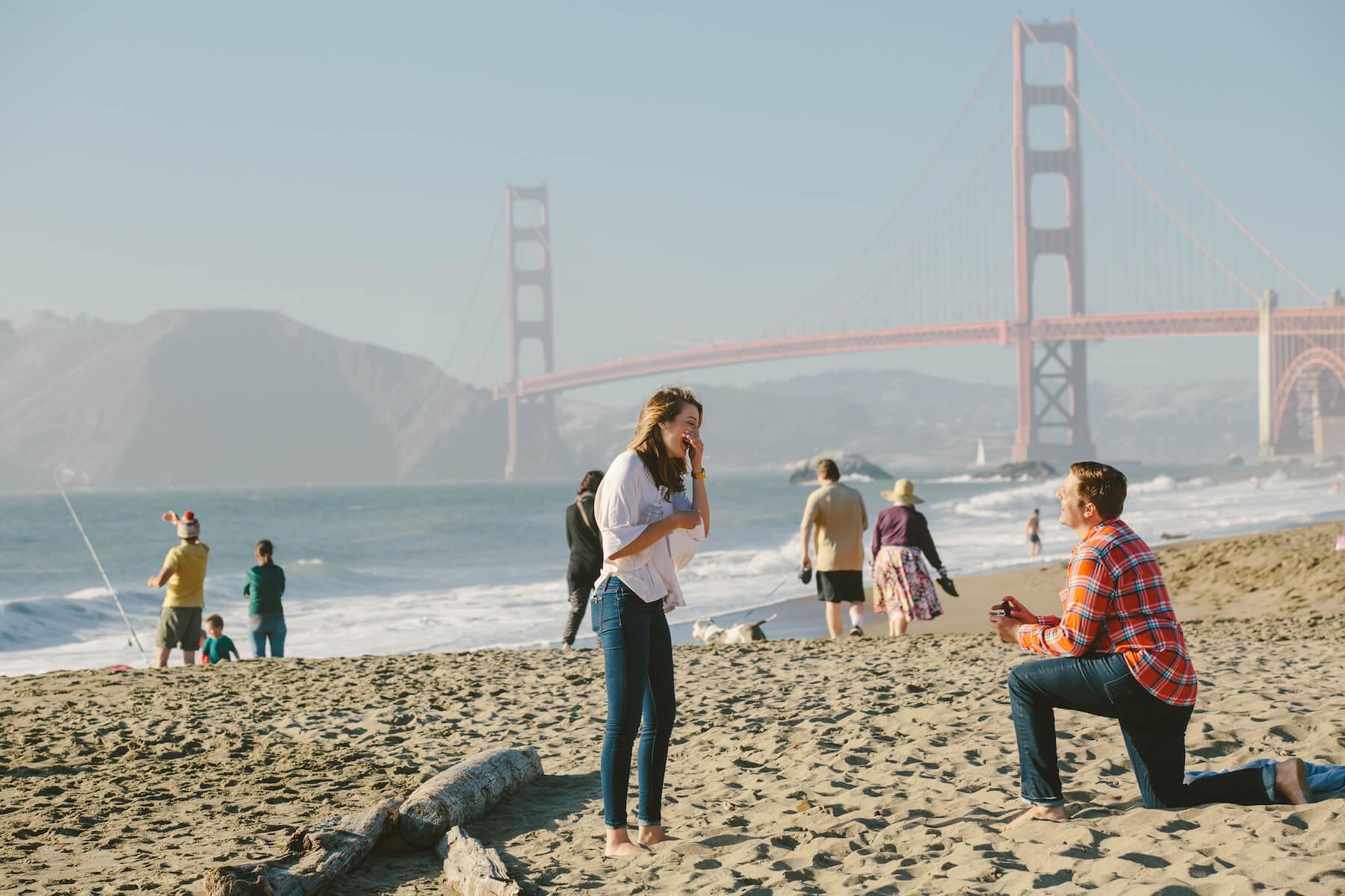 Man proposing to his partner on a beach in San Francisco, California, USA