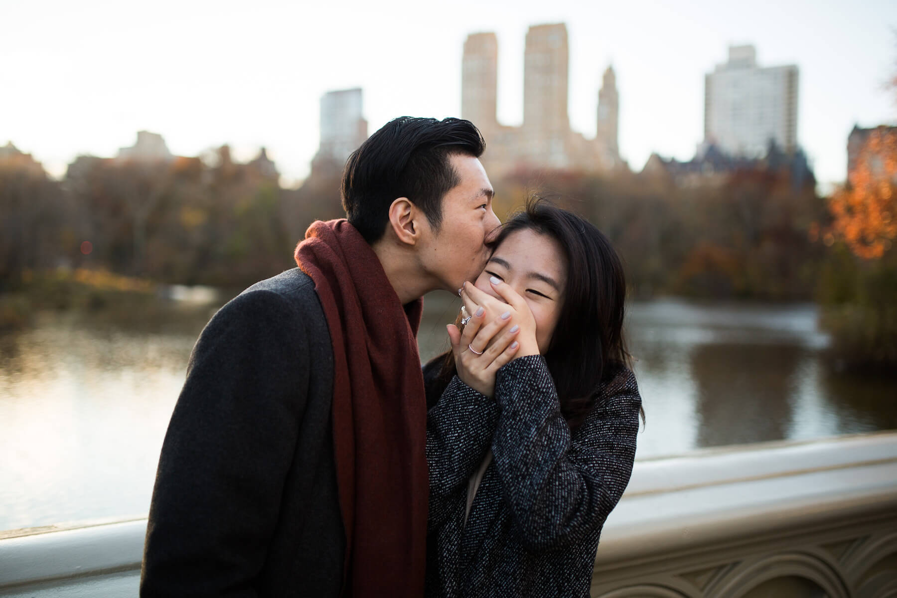 Man kissing his partner's forehead while she is covering her mouth smiling in Central Park, New York City, USA
