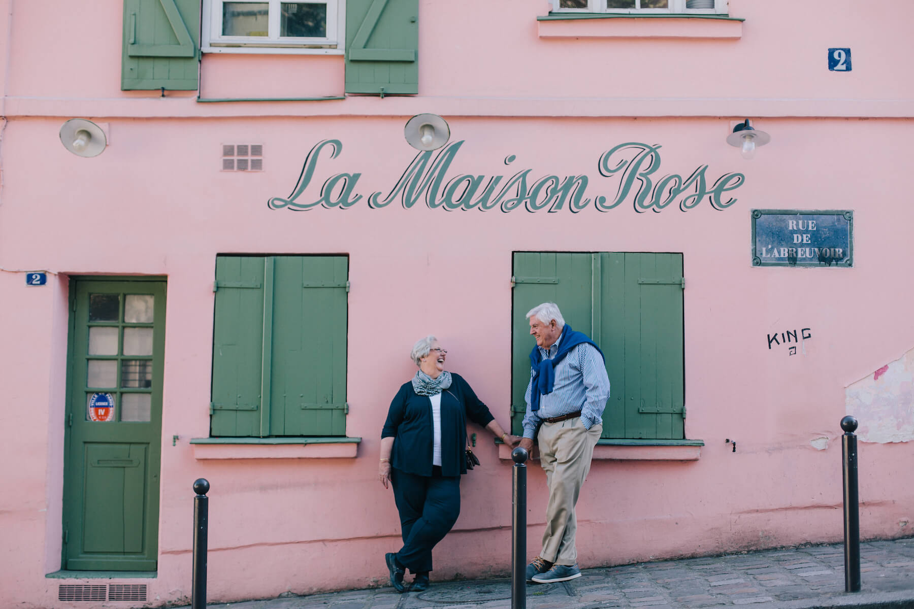 Mature couple laughing together in front of pink feature wall at La Maison Rose in Paris, France