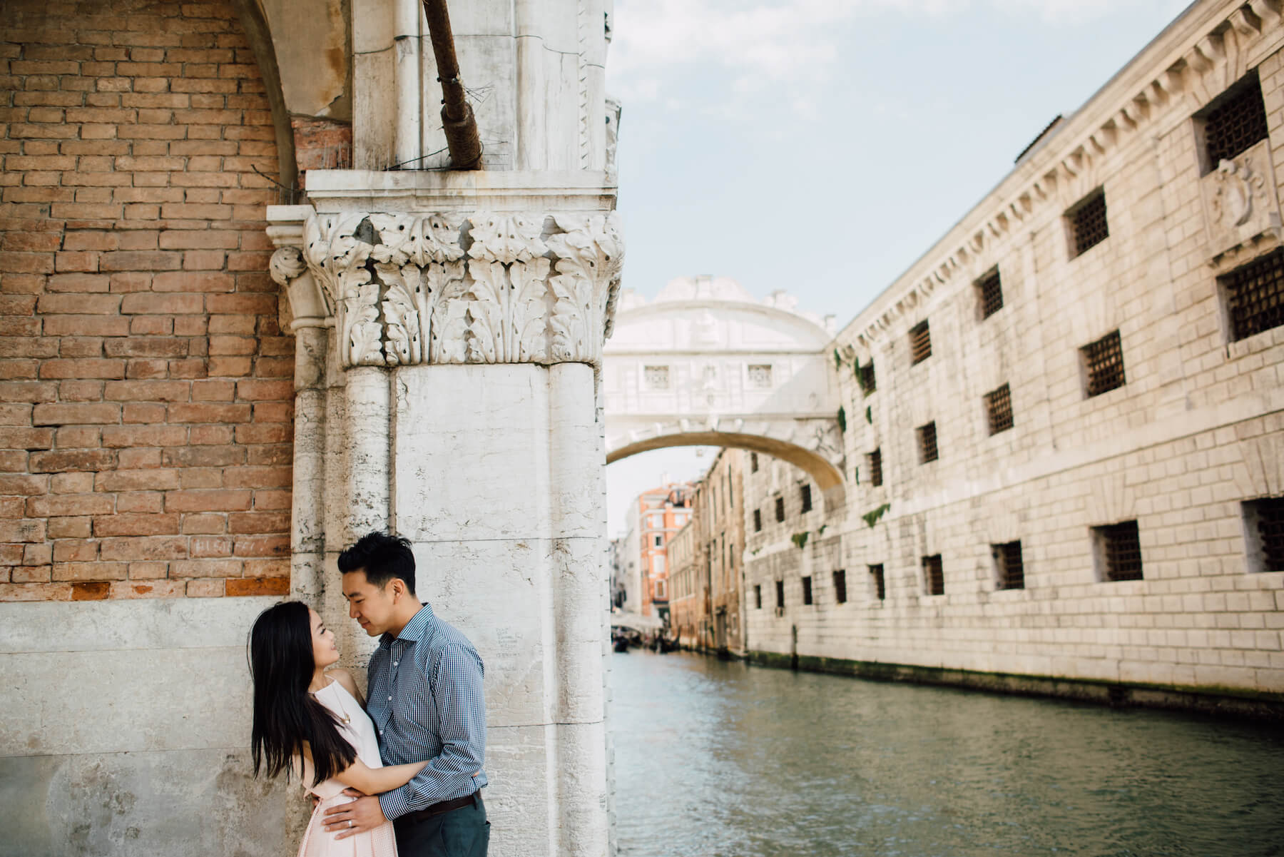 Couple holding each other at the edge of the canal in Venice, Italy