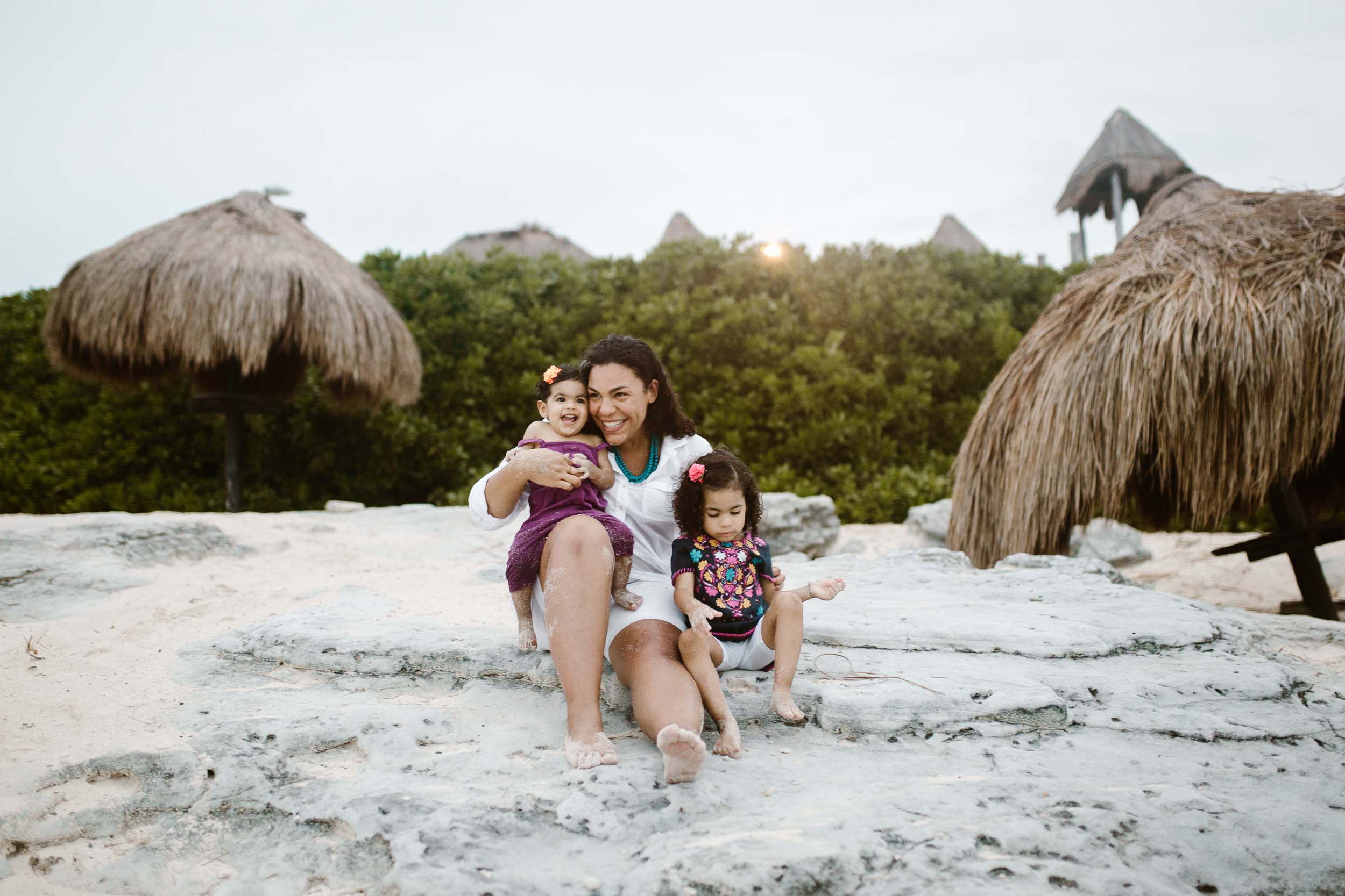 Mother and her two young daughters sitting on the beach in Cancun, Mexico