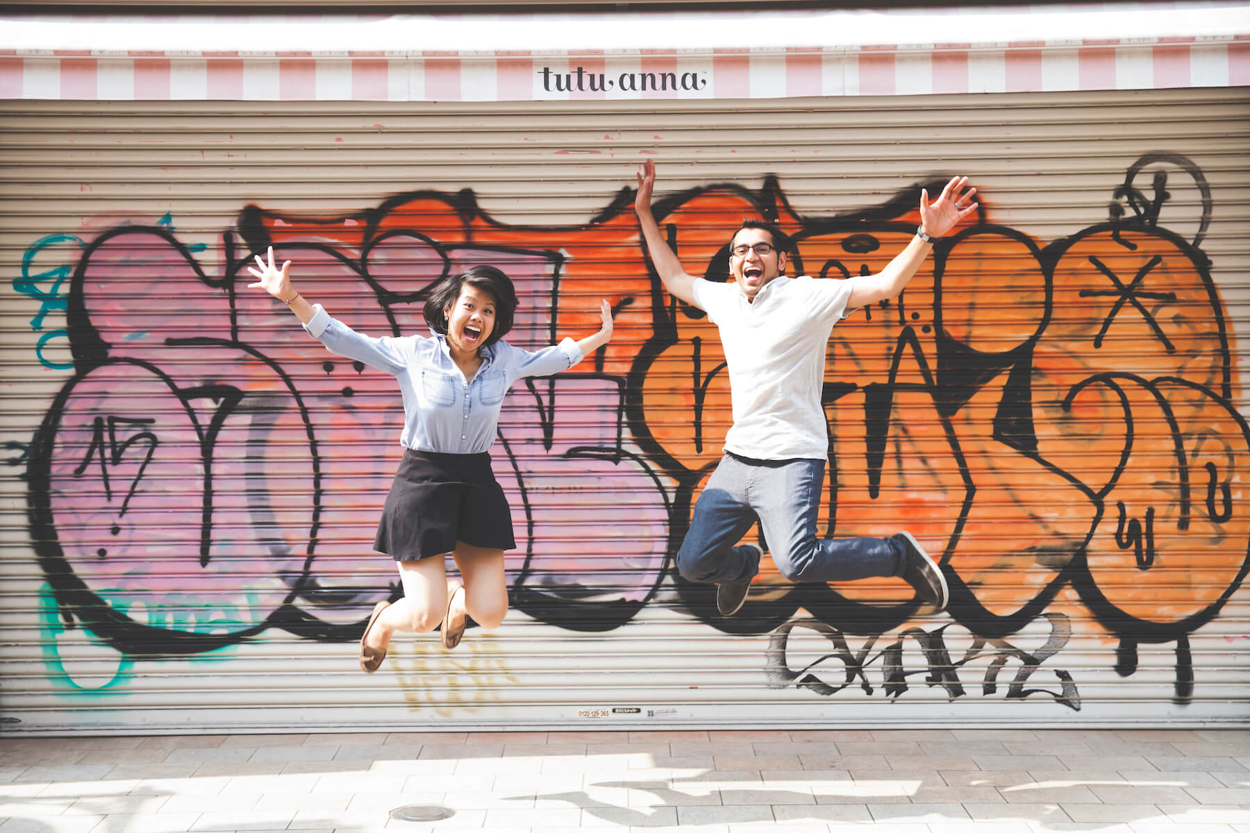 Couple jumping up in the air smiling in front of a graffiti wall in Tokyo, Japan